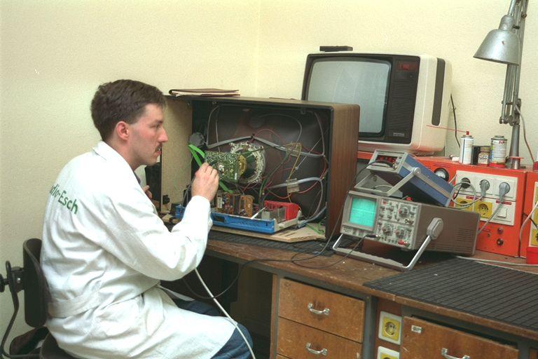 Ein Techniker beim überprüfen eines Fernsehers